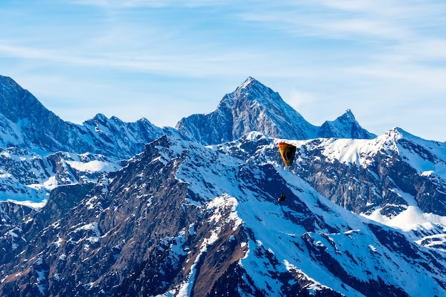 Schöne landschaft der schneebedeckten berge mit einem gleitschirm in südtirol, dolomiten, italien