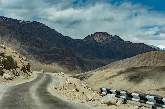 Schöne landschaft der straße auf dem weg im hügel mit schneegebirgshintergrund, ladakh