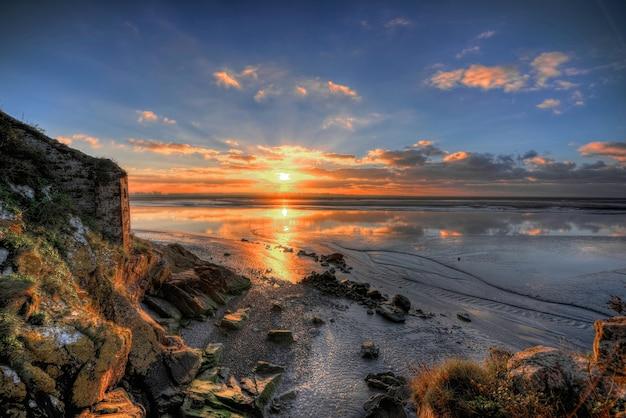Schöne landschaft des atemberaubenden sonnenaufgangs, der sich im meer spiegelt
