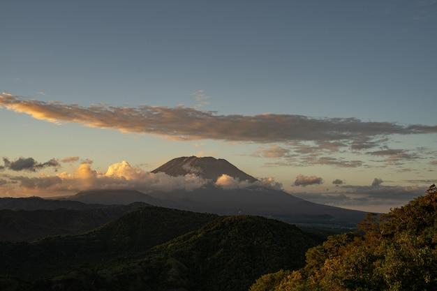 Schöne landschaft des bergtals und des majestätischen vulkans, umgeben von dichten wolken stockfoto