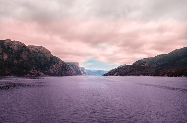 Schöne landschaft des meeres, umgeben von hohen felsformationen unter den gewitterwolken in norwegen