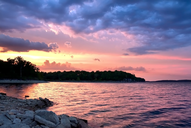 Schöne landschaft des sonnenuntergangs, der sich im meer unter den atemberaubenden bunten wolken spiegelt