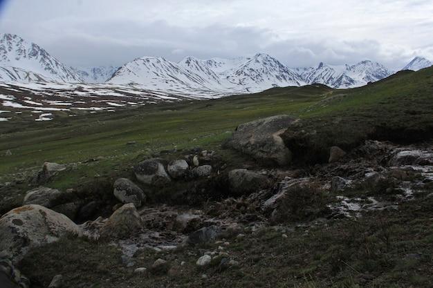 Schöne landschaft einer gebirgslandschaft mit felsigen hügeln, die mit schnee bedeckt sind