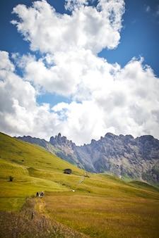Schöne landschaft einer grünen landschaft mit hohen felsigen klippen unter weißen wolken in italien