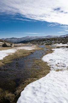 Schöne landschaft einer schneebedeckten landschaft mit felsigen klippen unter einem bewölkten himmel