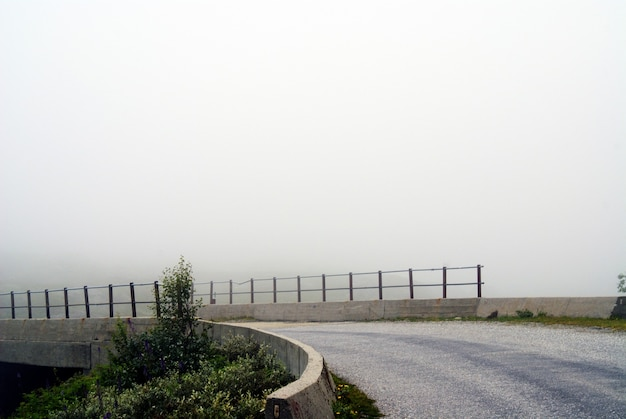 Schöne landschaft einer straße an einem düsteren tag mit einem nebligen hintergrund in norwegen