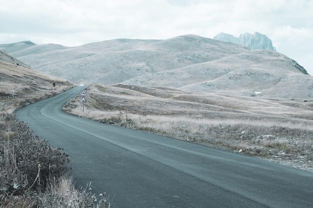 Schöne landschaft einer straße sanfte hügel an einem wolkigen tag