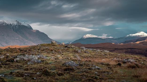 Schöne landschaft eines feldes, umgeben von hügeln unter dem düsteren himmel