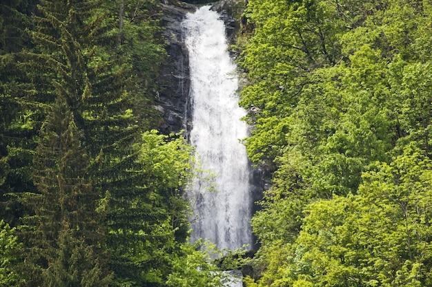 Schöne landschaft eines mächtigen wasserfalls, umgeben von viel grün