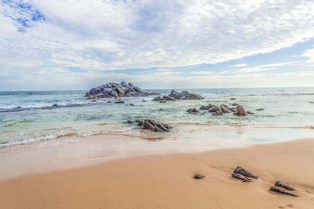 Schöne landschaft eines sandstrandes mit felsen im ozean gegen einen blauen himmelhintergrund.