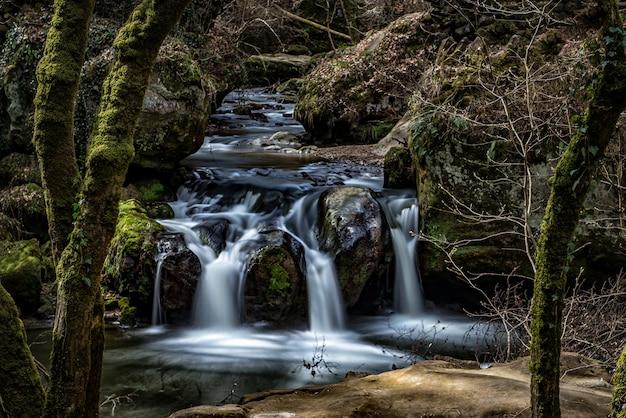 Schöne landschaft eines wasserfalls im wald, umgeben von felsformationen