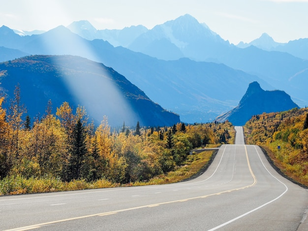 Schöne landschaft eines weges, umgeben von hohen felsigen bergen und grün unter einem bewölkten himmel