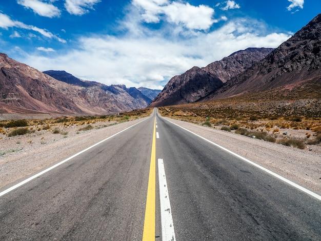 Schöne landschaft eines weges, umgeben von hohen felsigen bergen unter einem bewölkten himmel
