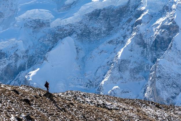 Schöne landschaft mit bergen, blauem riesigem gletscher und silhouette eines mannes, der mit einem großen rucksack und einer gitarre auf dem hintergrund von bergen und gletschern geht