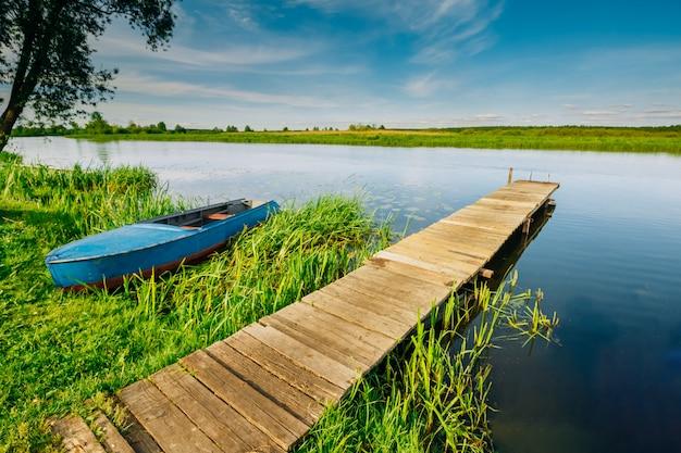 Schöne landschaft mit boot und pier am fluss