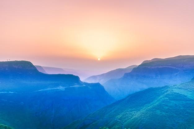 Schöne landschaft mit grünen bergen und herrlichem bewölktem himmel bei sonnenuntergang
