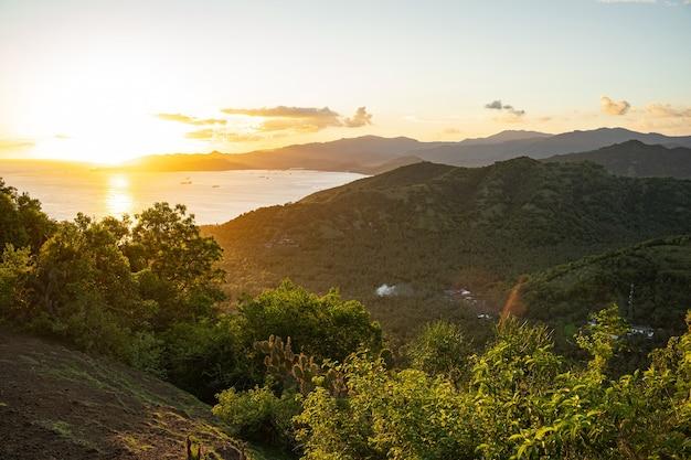 Schöne landschaft mit grünen t-stücken, bergen und meer mit hellem morgenhimmel im hintergrund stockfoto