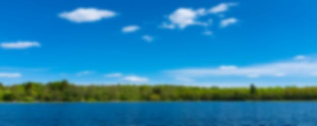 Schöne landschaft mit himmel, wasser und wolken mit wald am horizont