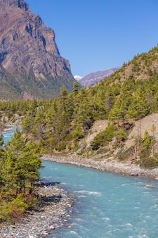 Schöne landschaft mit hohen himalaya-bergen, geschwungenem fluss, grünem wald und blauem himmel im herbst in nepal. bergtal. reisen im himalaya