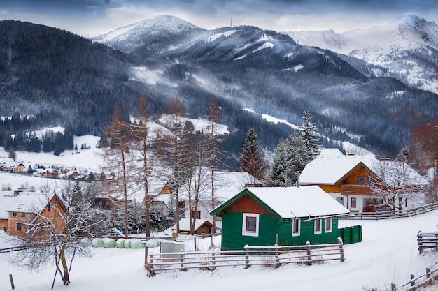 Schöne landschaft mit traditionellen holzhäusern auf hohen bergen, die von schnee bedeckt sind