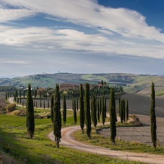 Schöne landschaft mit zypresse und straße im tal, sonnigem tag und wolken im himmel
