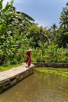 Schöne landschaft. nette junge weibliche person, die in der nähe des sees steht, während sie fische im wasser betrachtet