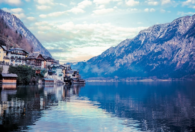 Schöne landschaft von gebäuden am see, umgeben von bergen in hallstatt, österreich