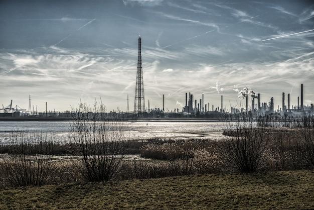Schöne landschaft von industriegebäuden am ufer, umgeben von gras unter atemberaubendem himmel