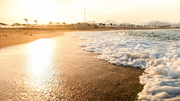 Schöne landschaft von meereswellen, die über das ufer gegen die sonnenuntergangssonne am himmel brechen. perfekter hintergrund für ihre sommerurlaubsreise