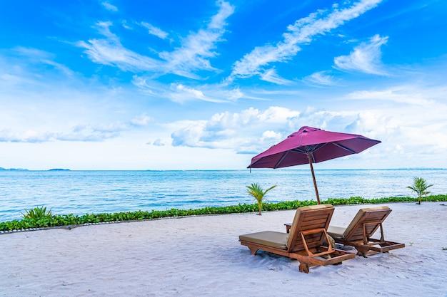 Schöne landschaft von strandseeozean mit leerer stuhlplattform und fast kokosnusspalme des regenschirmes mit weißer wolke und blauem himmel