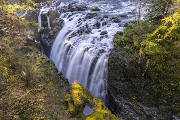 Schöne landschaftsaufnahme von wasserfällen, die eine grüne klippe hinunterfließen