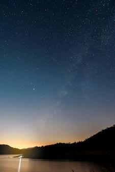 Schöne landschaftsberge und -see in der nacht mit milchstraßenhintergrund, chiang mai, thailand
