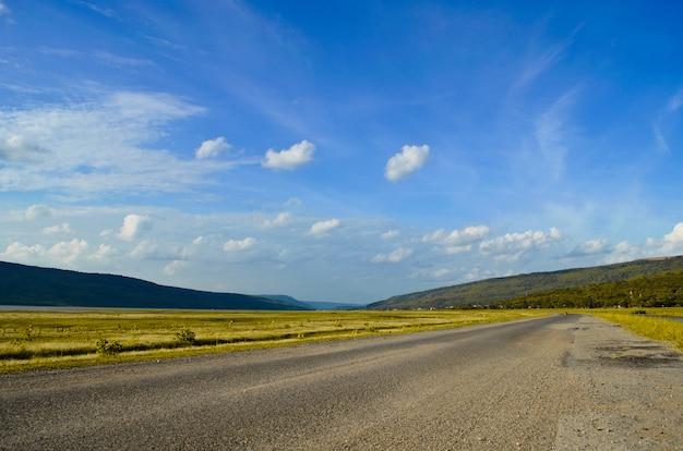 Schöne landstraße und blauer himmel zwischen ländlichem feld.