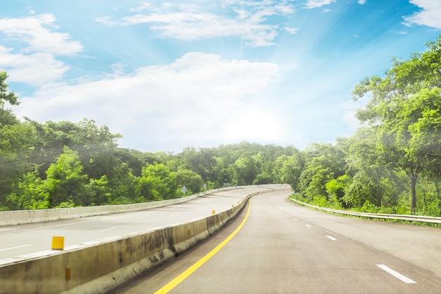 Schöne landstraßenstraße von thailand mit hintergrund des grünen berges und des blauen himmels