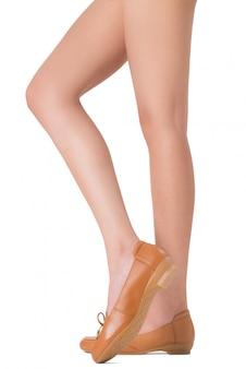 Schöne lange beine der frau mit den gekreuzten beinen werfen die tragenden lederschuhe auf, die auf weiß lokalisiert werden