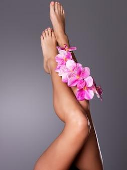Schöne lange weibliche beine mit blume. schönheitsbehandlungskonzept