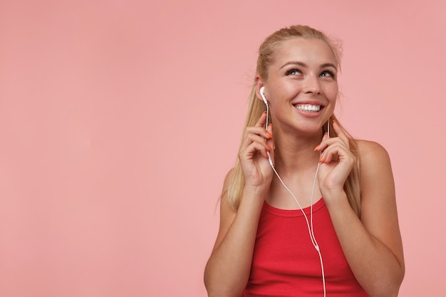 Schöne langhaarige blonde frau mit kopfhörern, die lieblingsmusik hören, fröhlich lächeln und nach oben schauen