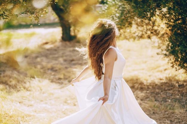 Schöne langhaarige braut in einem ausgezeichneten weißen kleid, das in natur geht