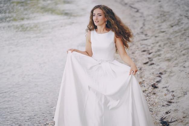 Schöne langhaarige braut in einem ausgezeichneten weißen kleid gehend auf einen strand