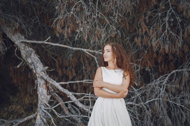 Schöne langhaarige braut in einem ausgezeichneten weißen kleid in der natur