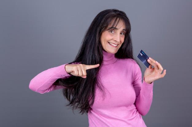 Schöne langhaarige brünette frau in ihren 40ern lächelt und zeigt ihre kreditkarte
