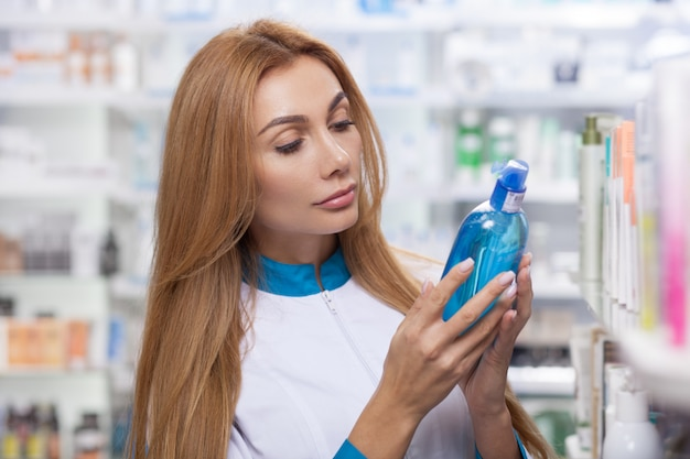Schöne langhaarige chemikerin, die produkte zum verkauf in ihrer drogerie untersucht