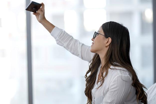 Schöne lateinamerikanische frau, die ein selfie in ihrem schlafzimmer macht, während sie eine pause macht