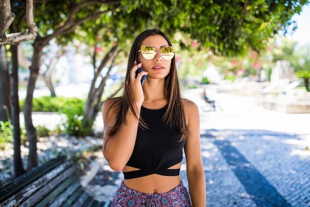 Schöne lateinische frau, die am telefon spricht und in einem park lächelt