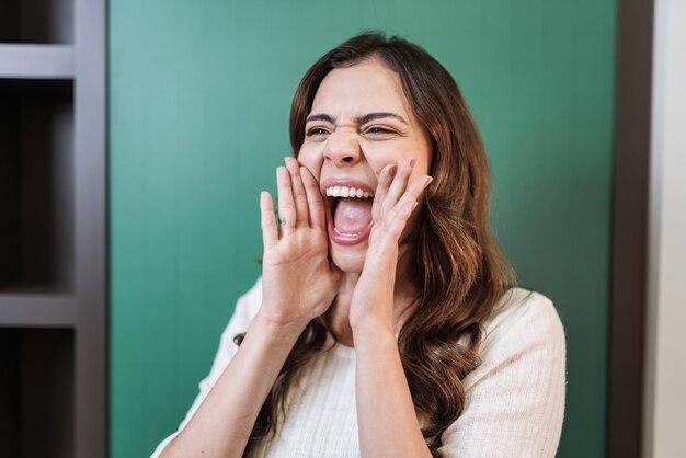 Schöne lateinische frau, die mit der hand auf dem mund laut schreit. kommunikationskonzept.