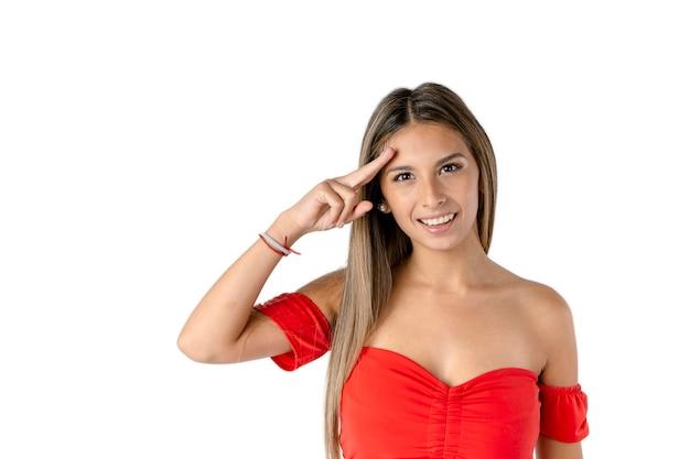 Schöne lateinische frau, die vorwärts mit ihrer hand auf ihrer stirn und mit einer glücklichen haltung auf einem reinweißen hintergrund winkt.
