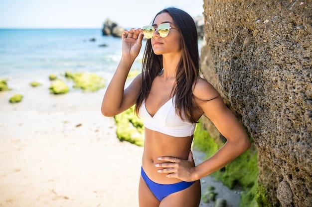 Schöne lateinische frau im bikini auf dem klippenstrand in der ozeanküste.