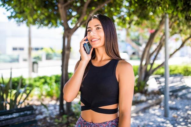 Schöne lateinische junge frau, die am telefon beim gehen auf der straße spricht