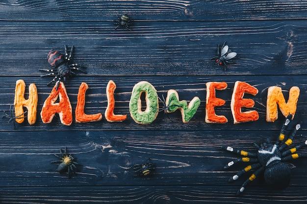 Schöne lebkuchenbuchstaben für halloween mit spinnen und käfern auf dem tisch. süßes oder saures ansicht von oben