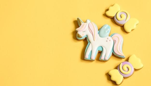 Schöne lebkuchenkekse für kinderparty in form eines einhorns und süßigkeiten, flach gelegt.